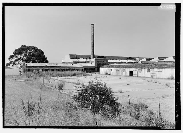 Ford Richmond Assembly Plant VIEW TO SOUTHWEST SHOWING OIL HOUSE (LEFT), BOILER ROOM AND STACK (CENTER), ROOF OF CRANEWAY (BACKGROUND), AND CRATING SHED (RIGHT).